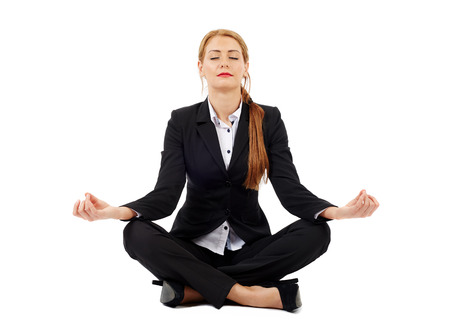 Photo for Beautiful businesswoman sitting in lotus position of yoga, isolated on white - Royalty Free Image