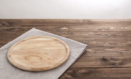 Foto de Background for product montage. Empty round wooden board with tablecloth. - Imagen libre de derechos