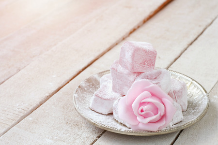 Photo for Turkish delight with rose flavor in  metal plate, pink rose flower on wooden table, closeup - Royalty Free Image