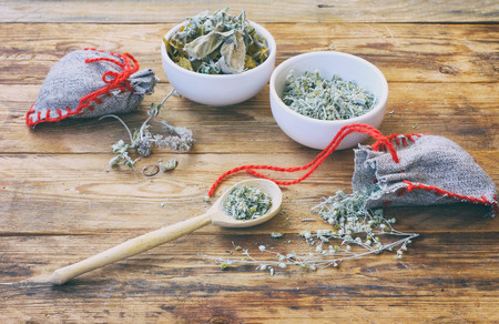 Foto de homemade sachets with wormwood, two white bowls with dry herbs, on wooden table closeup - Imagen libre de derechos