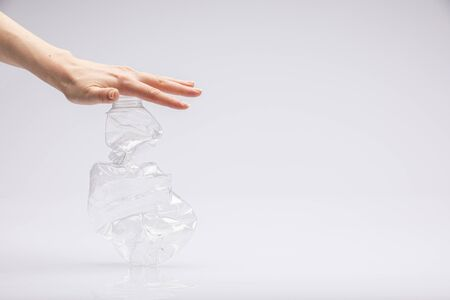 Photo pour Close-up of a white people's hand crushing a crumpled plastic bottle in front of a white background - image libre de droit
