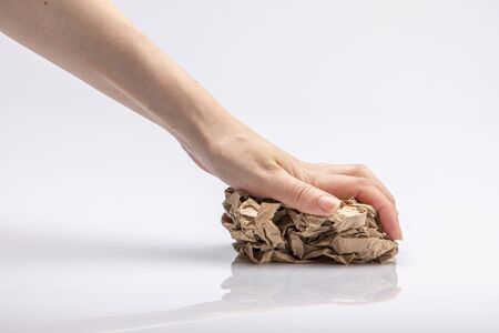 Photo pour Close-up of a white people's hand crushing a crumpled piece of brown paper in front of a white background - image libre de droit