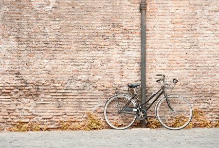 Photo pour old black bicycle against a bricks wall - image libre de droit