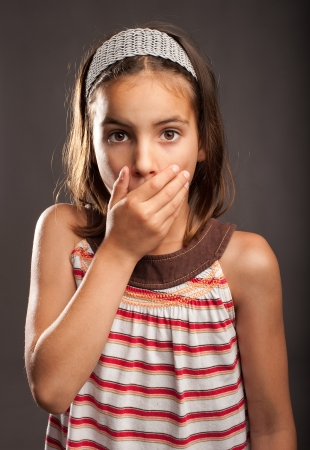 little surprised girl covering mouth with her hand