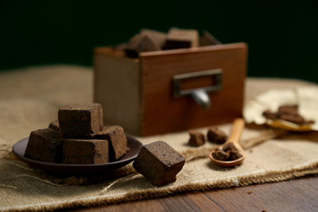 Photo pour Brown sugar chunks in wooden boxes and plates - image libre de droit