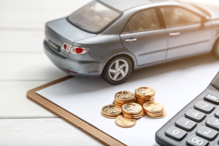 Foto de car model,calculator and coins on white table - Imagen libre de derechos
