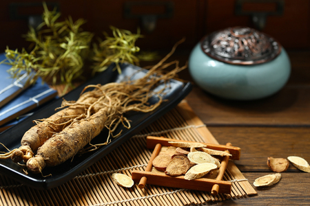 Photo for  ginseng in black plate on wooden table - Royalty Free Image