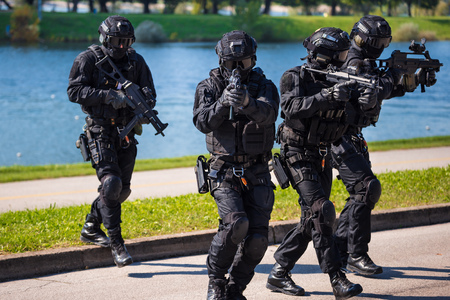 Foto de Special forces tactical team of four in action, unmarked and unrecognizable swat team - Imagen libre de derechos