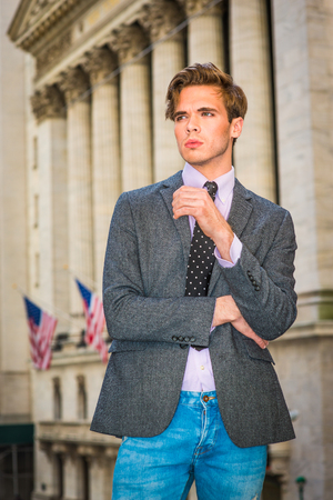 Photo pour Young blonde, handsome graduate student, wearing blazer, necktie, jeans, standing by vintage style office building with American flags, looking forward. Urban casual fashion. - image libre de droit