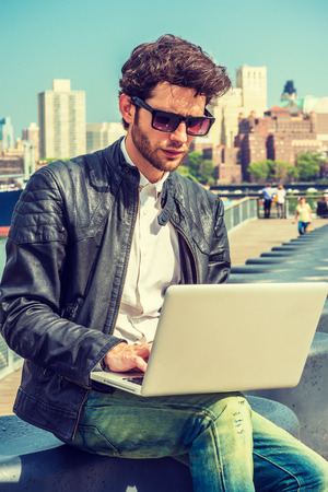 Photo pour European businessman traveling, working in New York. Wearing black leather jacket, blue jeans, sunglasses, a guy with beard, sitting on bench at deck on harbor, reading, working on laptop computer. - image libre de droit