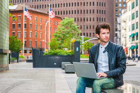 Photo pour European businessman working on street in New York. Wearing leather jacket, jeans, young guy with beard, sitting on marble bench, thinking, working on laptop computer. American flags on background. - image libre de droit