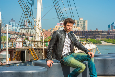 Photo pour European businessman traveling in New York. Wearing black leather jacket, blue jeans, a young guy with beard, sitting on bench at harbor, frowned, sad, missing family, friends. A boat on background. - image libre de droit