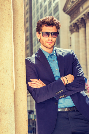 Photo pour Serious European businessman traveling, working in New York. Dressing in blue suit, wearing sunglasses, a young guy with beard standing in business district, crossing arms, thinking. Filtered effect. - image libre de droit