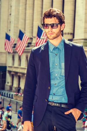 Photo pour Serious European businessman in New York. Dressing in blue suit, shirt, wearing sunglasses, a young handsome guy with beard standing in business district, looking down, thinking. Filtered effect. - image libre de droit