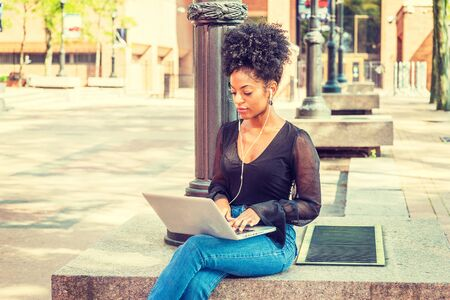 Photo pour Young African American Woman with afro hairstyle wearing mesh sheer long sleeve shirt, jeans, sitting by light pole on campus in New York, listening music with earphone, working on laptop computer - image libre de droit