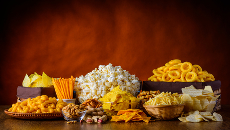 Photo pour Different types of snacks, chips, nuts and popcorn in still life - image libre de droit