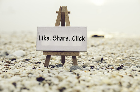Photo for conceptual image with word LIKE SHARE CLICK on white canvas frame with wooden tripod stand.Blurred Clamshell and cockles background. - Royalty Free Image