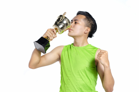 Foto per Happy expression young fit man in sportswear, holding and kissing gold trophy over white background - Immagine Royalty Free