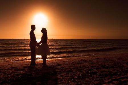 Photo pour Couple holding hands on the beach - image libre de droit