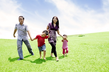 Happy asian family runing together in meadow shot outdoor