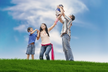 Photo pour Asian family spending a fun summer day in meadow  - image libre de droit