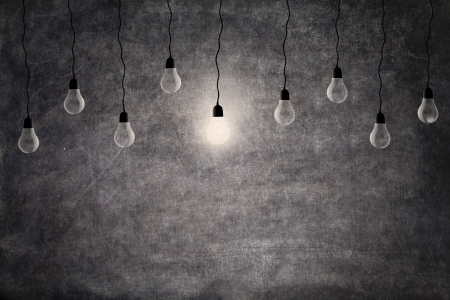 Photo for Bright idea concept  a glowing light bulb in front of empty blackboard with copy space - Royalty Free Image