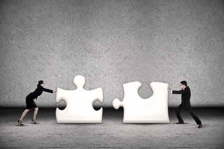 Foto de Two business people are working together to put two puzzles in order to succeed - Imagen libre de derechos