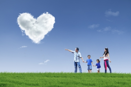 Photo for Happy family is walking in the park to see clouds of love - Royalty Free Image