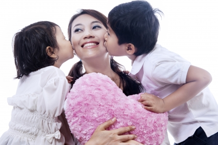Happy mother kissed by her daugher and son on white background