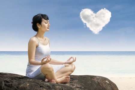 Photo pour Attractive woman exercise yoga under love cloud at beach - image libre de droit