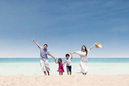 Foto de Happy Asian family running at beach - Imagen libre de derechos