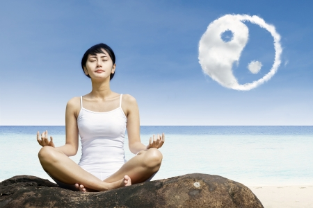 Photo pour Woman meditation and ying yang cloud at beach - image libre de droit
