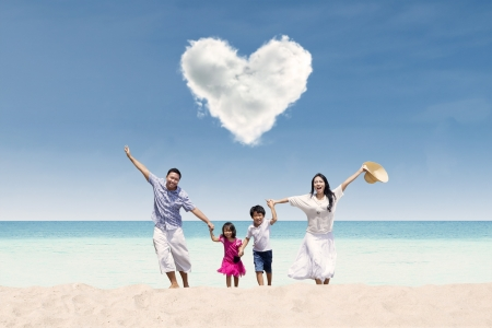 Photo pour Happy Asian family run at beach under love cloud - image libre de droit