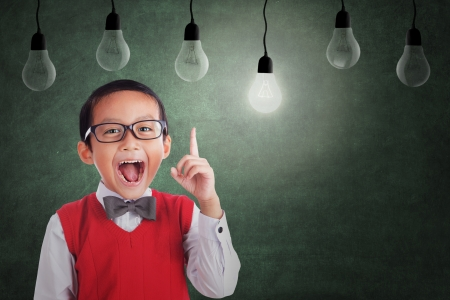 Foto de Asian student boy has an idea under light bulbs in class - Imagen libre de derechos