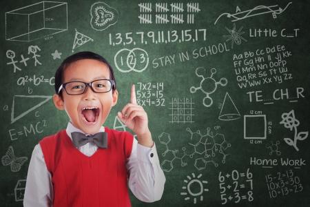 Foto de Cheerful boy student has idea in classroom - Imagen libre de derechos