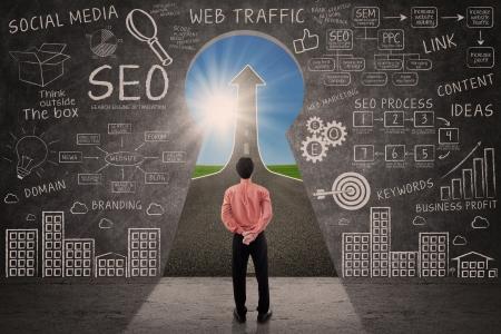 Foto de Businessman looking through key hole with SEO doodle on blackboard - Imagen libre de derechos