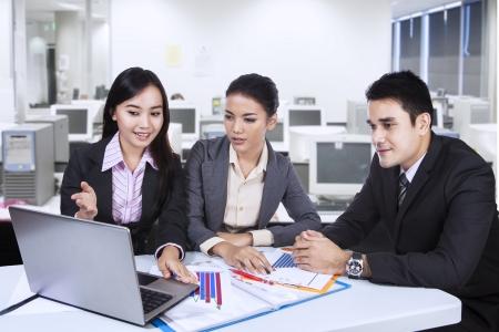 Foto de Three asian business team working with laptop at office - Imagen libre de derechos