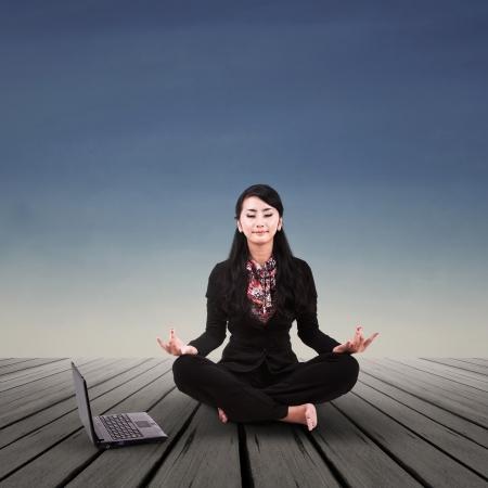 Foto de Asian businesswoman is meditating outdoor - Imagen libre de derechos