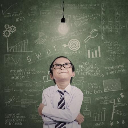 Foto de Little businessman looking at lit bulb with drawn formula on the board - Imagen libre de derechos