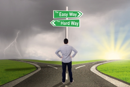 Photo for Businessman is standing on the road with sign of easy vs hard way - Royalty Free Image