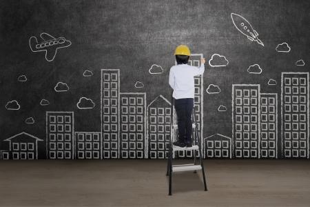 Foto de Businessman drawing cityscape standing on a ladder - Imagen libre de derechos