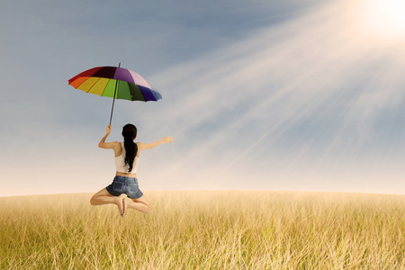Excited woman with colorful umbrella jumping  in rice field and sunset
