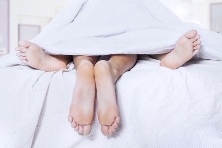 Photo pour Close-up of couple's feet having intimate relation in bed - image libre de droit