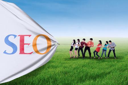 Foto de Portrait of business team pulling together a banner of SEO - Imagen libre de derechos