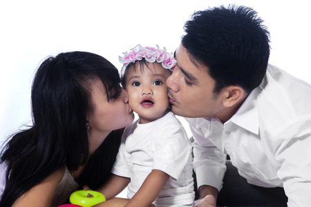Happy family with Asian parents kissing their baby girl isolated over white