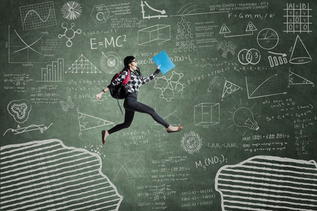 Photo for Female student jumping in classroom through gap on the blackboard - Royalty Free Image