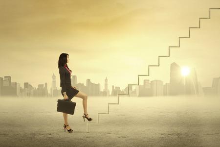 Foto de Young businesswoman walking up on stairs for succes - Imagen libre de derechos