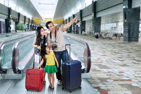 Photo pour Portrait of happy family in airport hall going to holiday and looking at something - image libre de droit