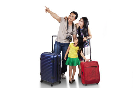 Photo pour Portrait of happy family carrying suitcase for holiday and looking at copyspace - image libre de droit