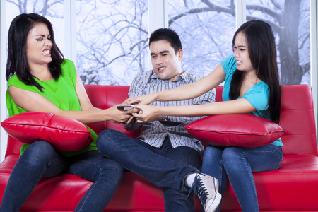 Three asian teenager sitting on sofa and fighting to take a remote control with winter background on the window